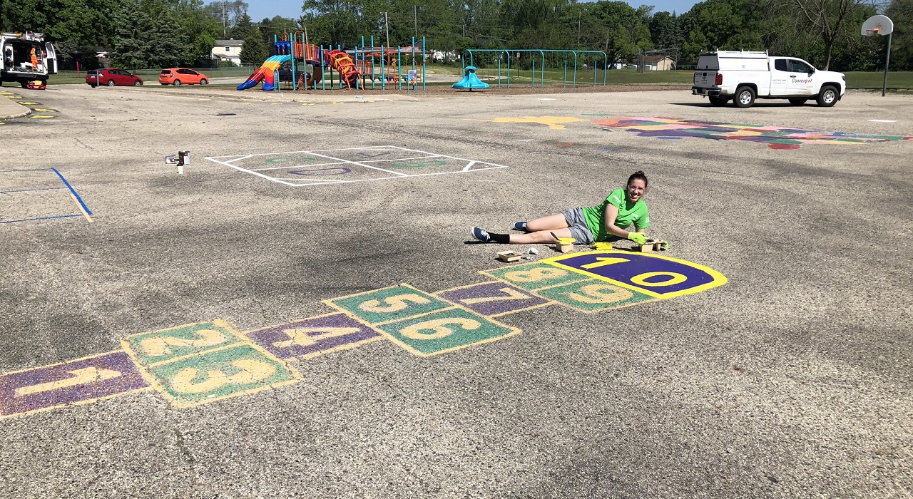 Colleague painting a hopscotch in a children's playground