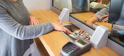 Person passing money to a bank teller