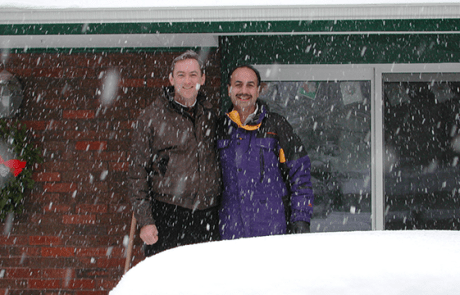Two men standing in front of a house with snow