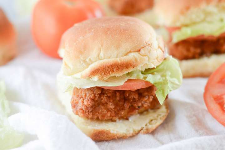 chicken slider with lettuce and tomato on a white surface