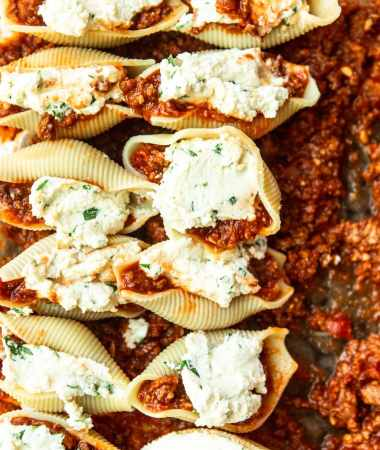 twelve shells filled with ricotta cheese on top of meat sauce