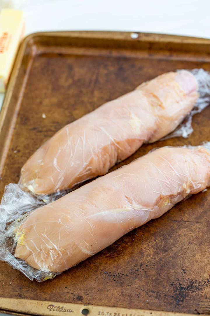 two chicken breasts rolled up in plastic on a baking sheet.