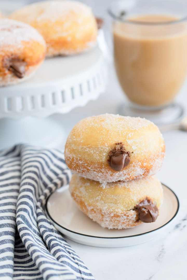 two nutella stuffed donuts on a small white plate with a blue and white towel on the side, a coffee and more donuts in the background.