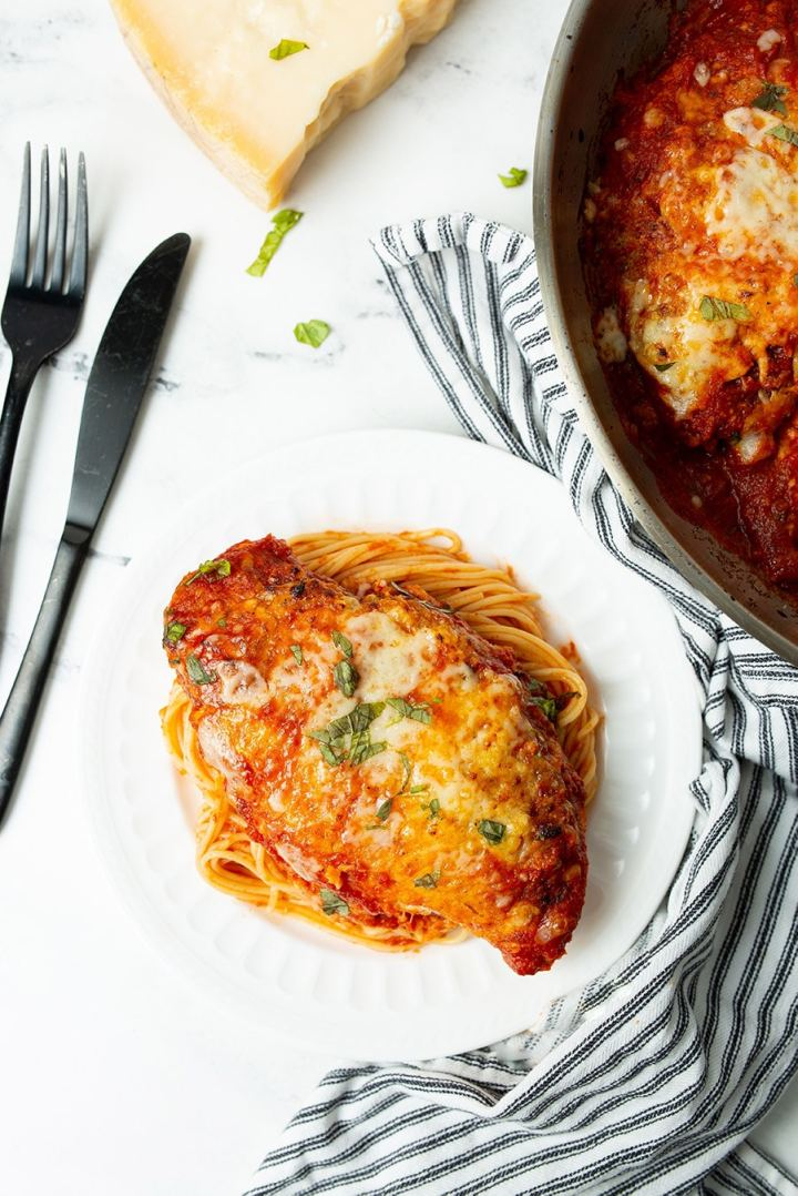 chicken parmigiana with spaghetti on a white plate with a knife and fork on the side and a blue and white towel.