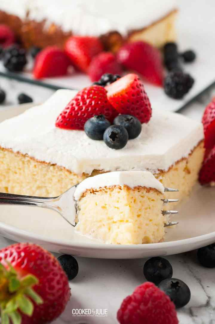 a slice of tres leches on a plate with berries and a fork