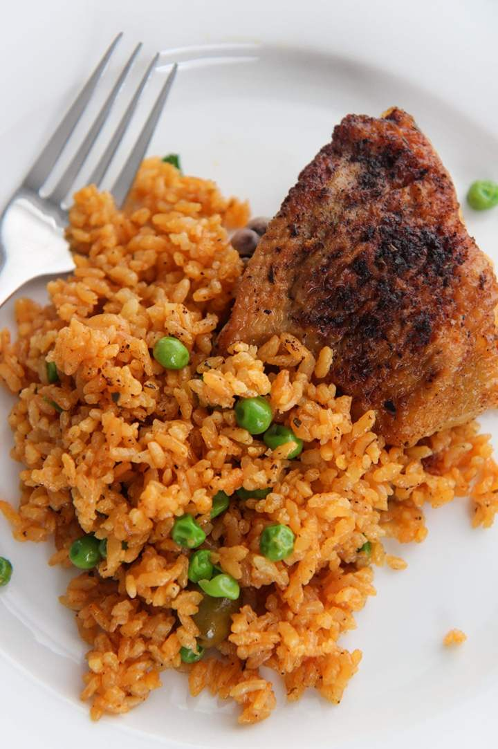 one chicken thigh and yellow rice with green peas on the side on a white plate with a fork.