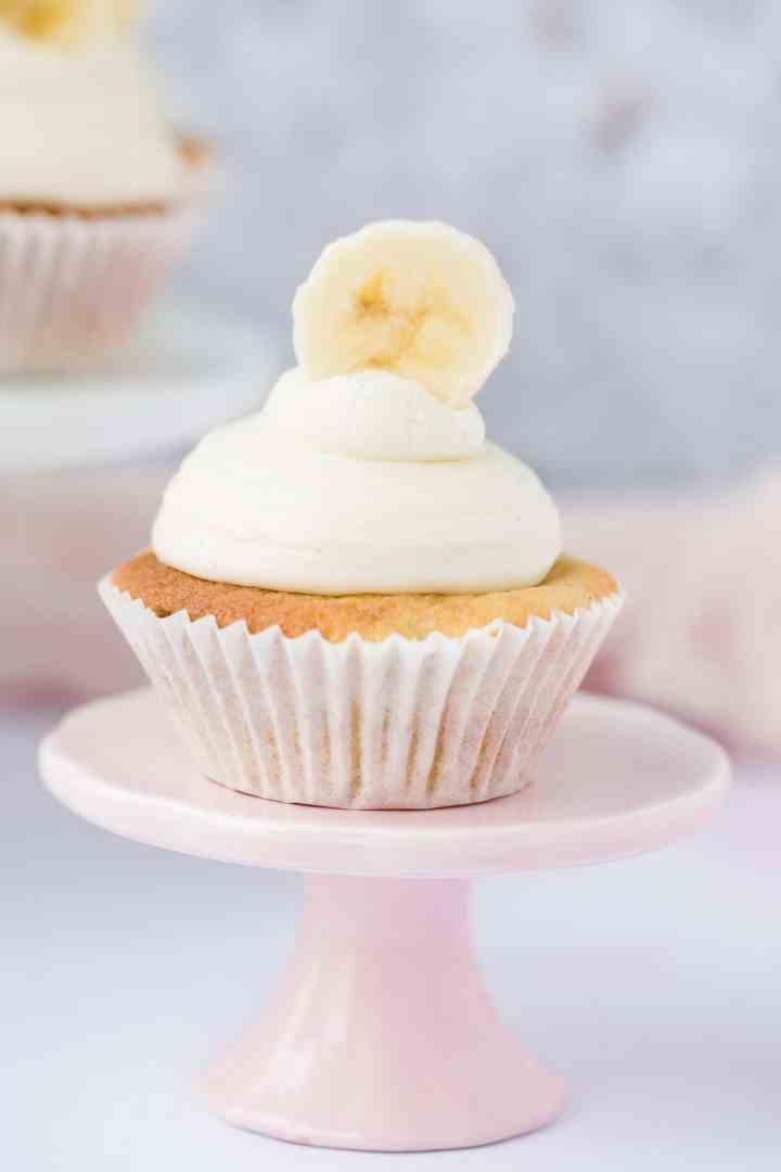 one banana cupcake on a small pink cake stand.