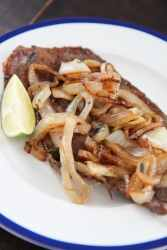 Cuban style steak and onions on a white plate with a lime wedge on the side.