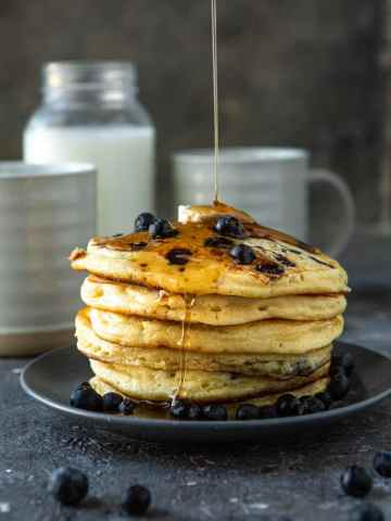 six blueberry pancakes on a blue plate with butter and maple syrup on top. A jug of milk in the background with two mugs and fresh blueberries.