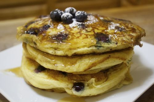 Fluffy blueberry filled pancakes with syrup and powdered sugar