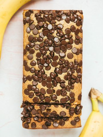 chocolate peanut butter banana bread with two bananas on the side