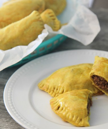 Jamaican beef patties in a basket and a white plate