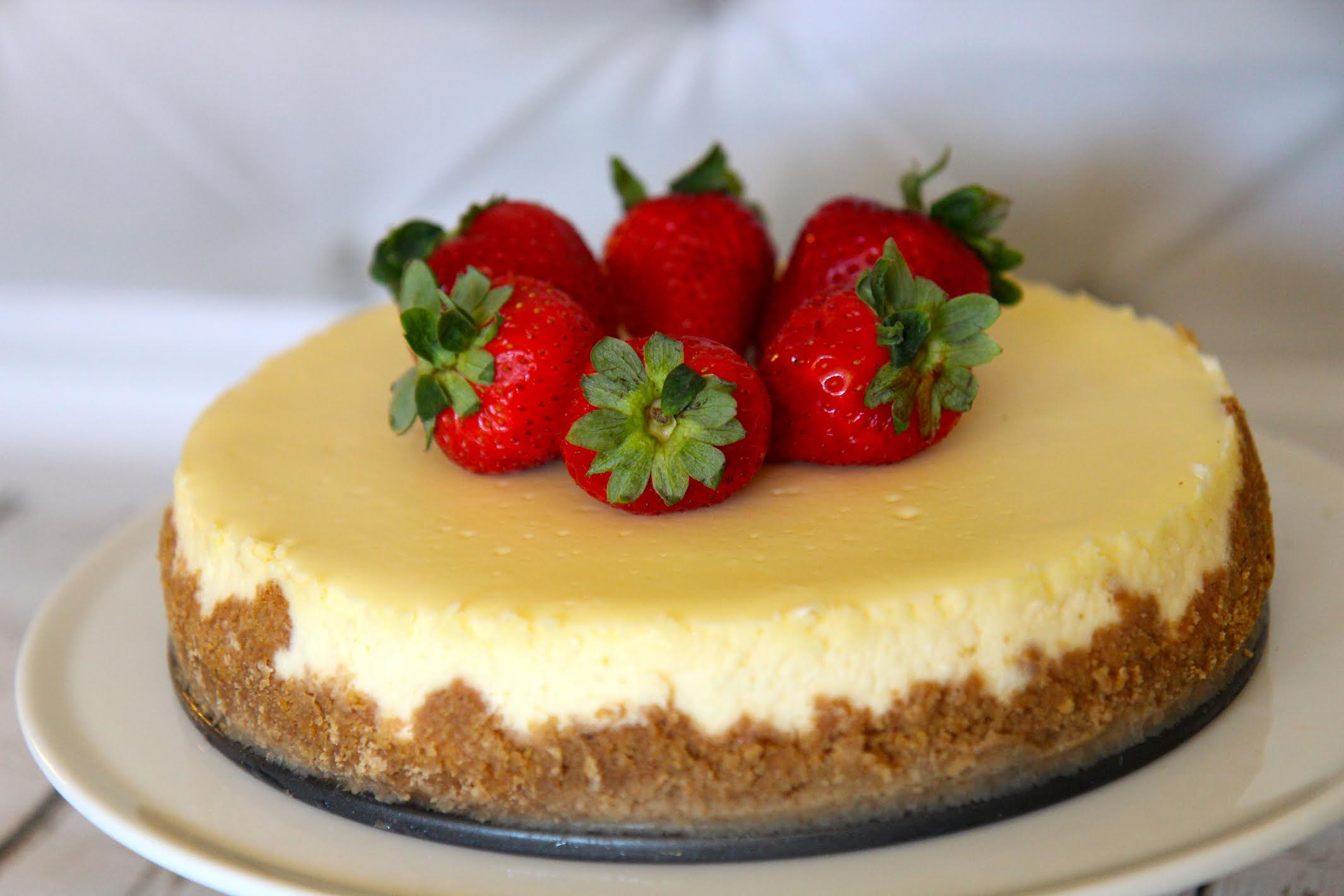 Plain Homemade cheesecake with a graham cracker crust and topped with strawberries.