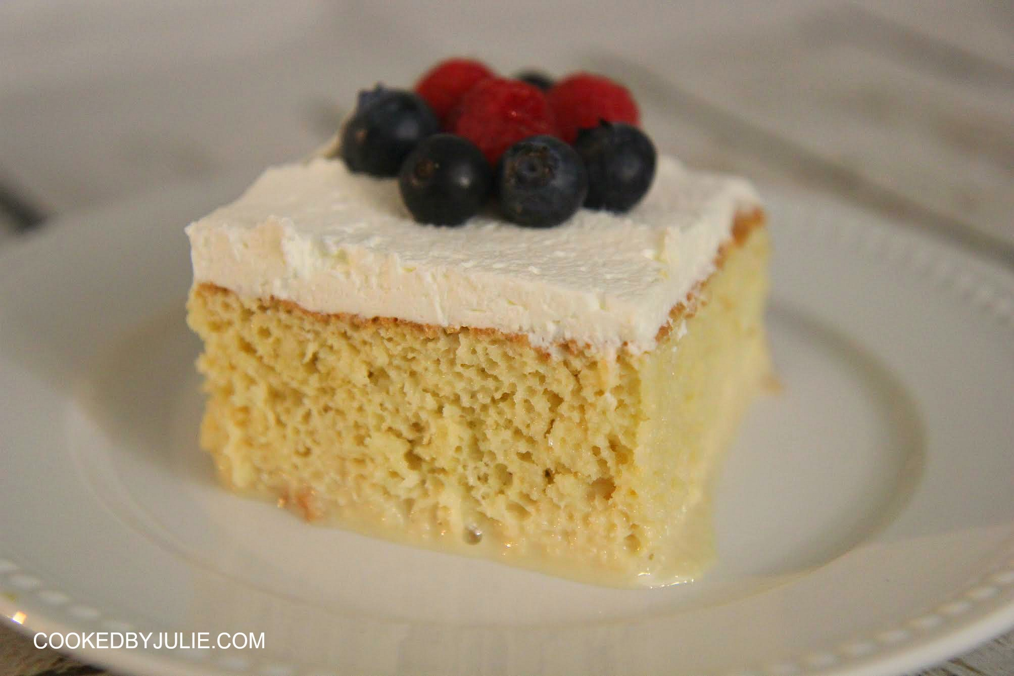This decadent and moist pastel de tres leches cake is a perfectly sweet dessert! Serve with a whipped cream topping and fresh raspberries and blueberries.