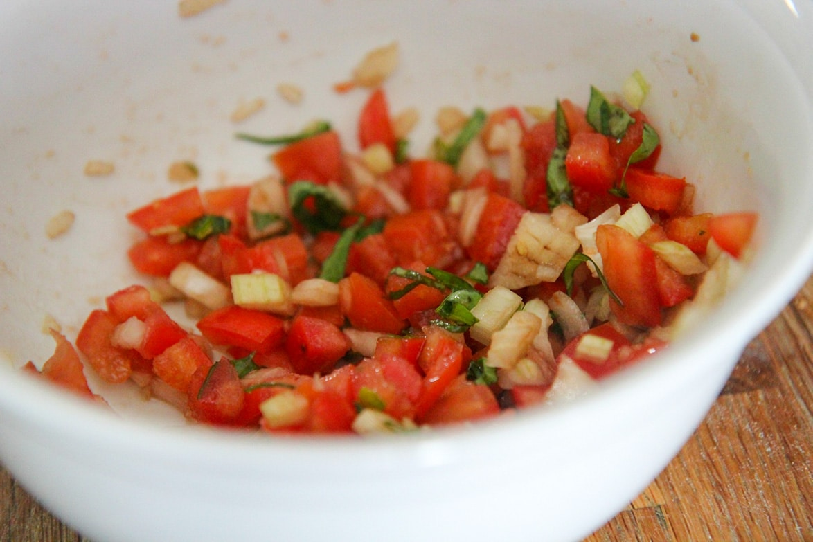 diced tomatoes, diced onions, and fresh sliced basil in a small white bowl.