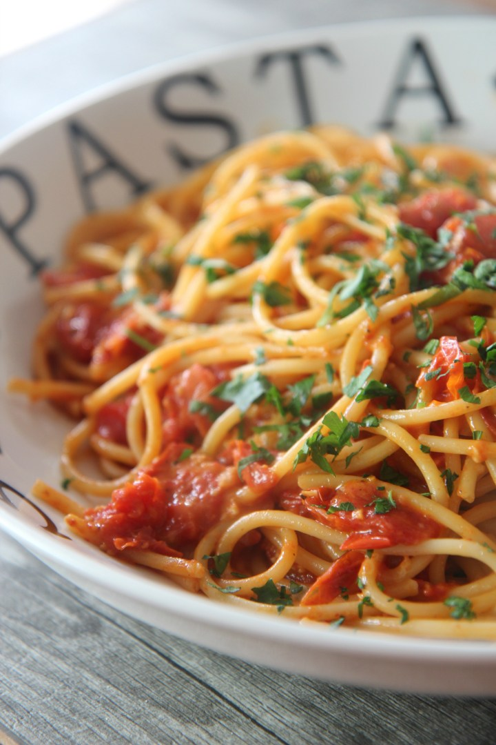 Tender angel hair pasta coasted in freshly roasted tomatoes and topped with parmesan cheese