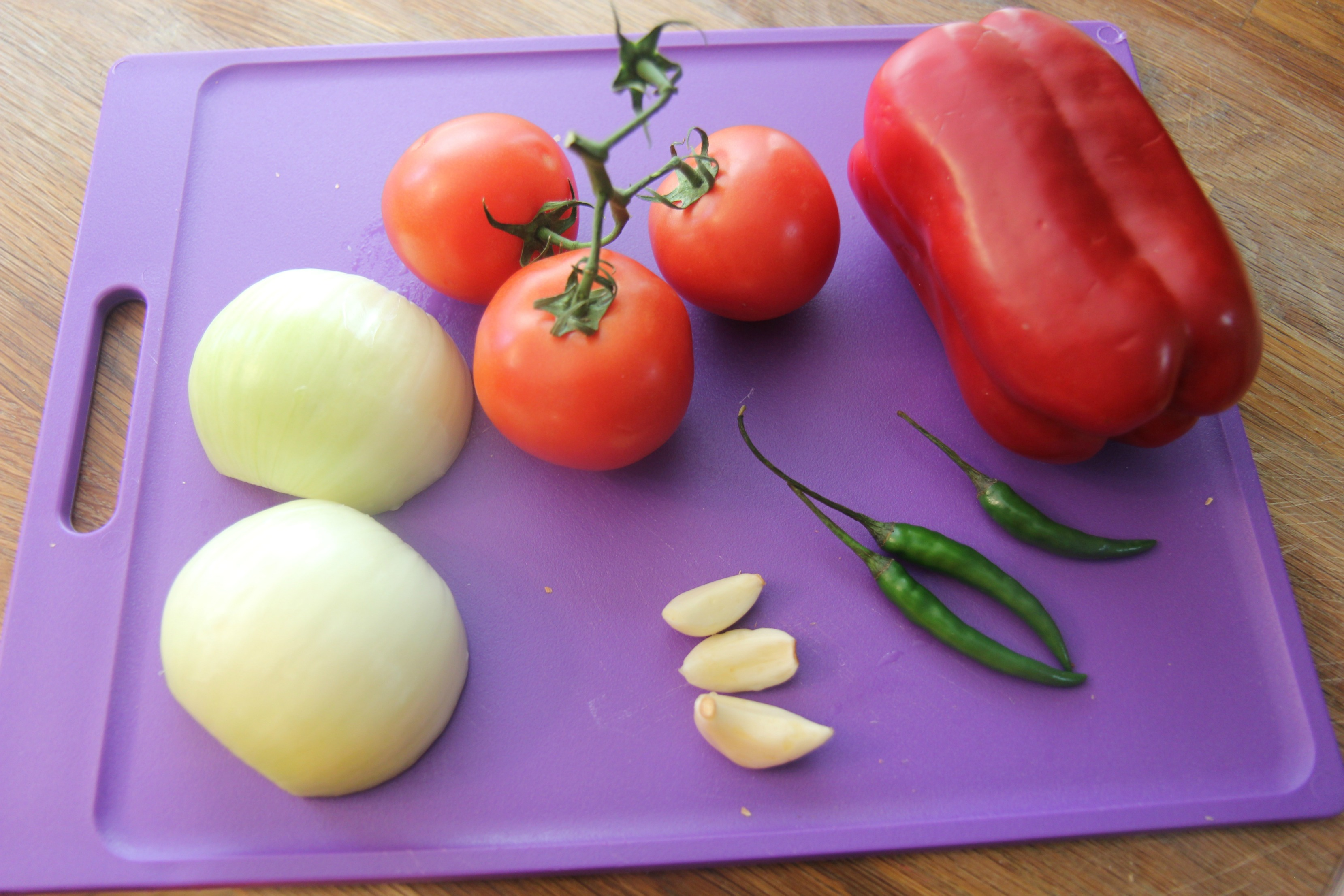 Spicy chicken tortilla soup ingredients on a purple cutting board.
