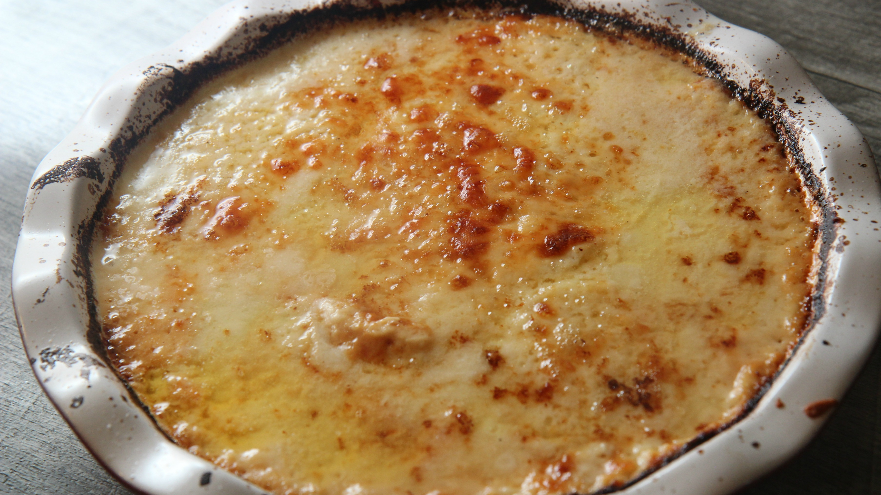 oven baked cheesy scalloped potatoes in a white pie dish: Cooked by Julie