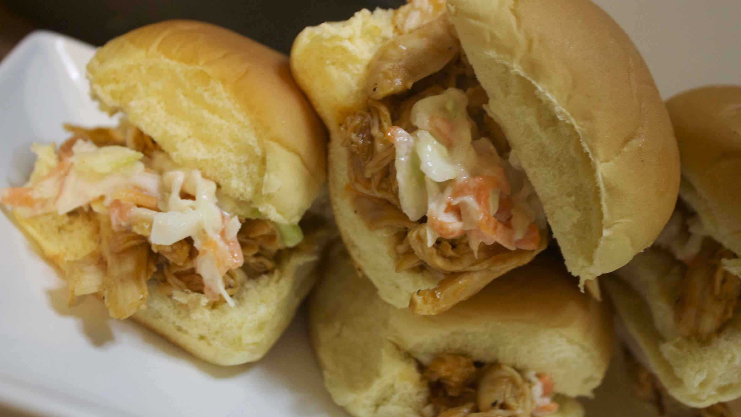 BBQ pulled chicken on soft dinner rolls topped with a sweet coleslaw
