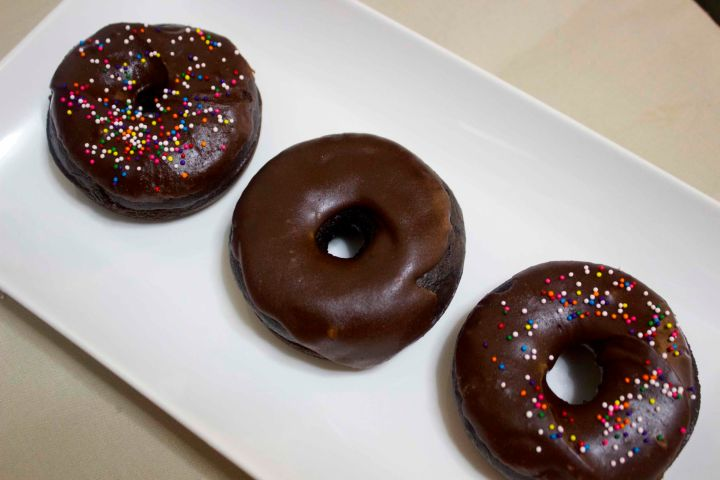 three frosted chocolate donuts