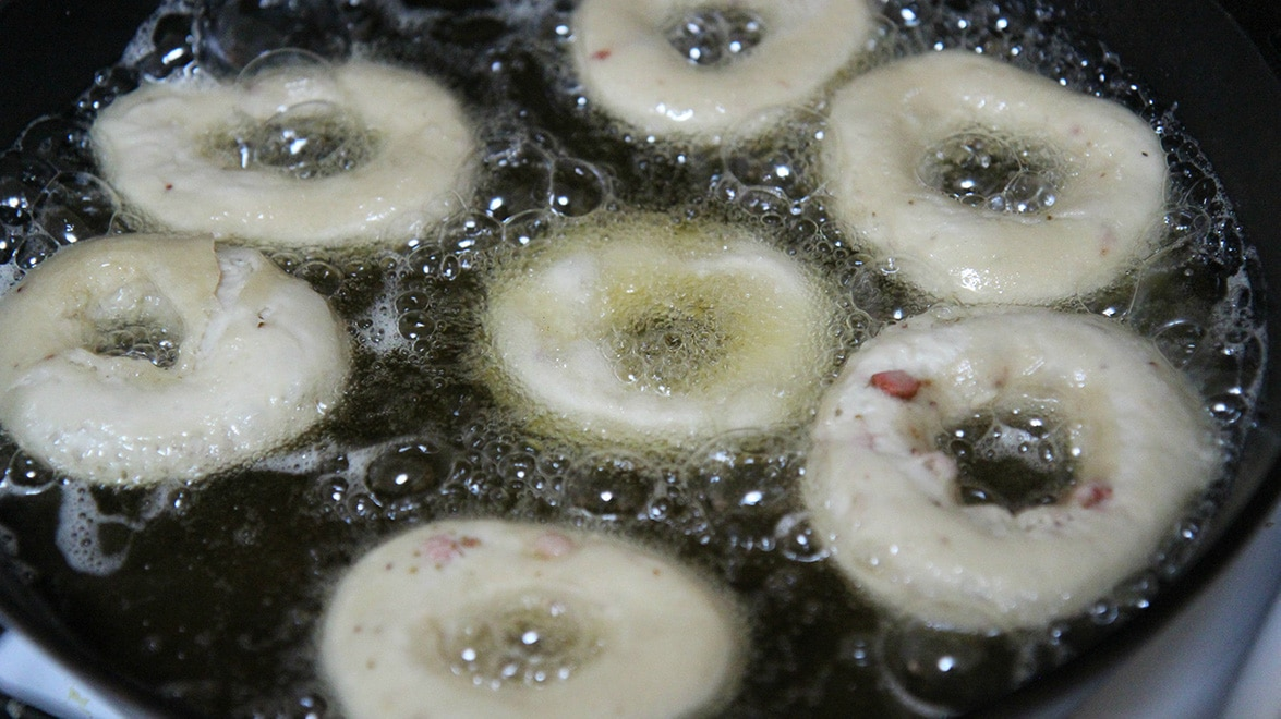 donuts frying in a skillet with oil.