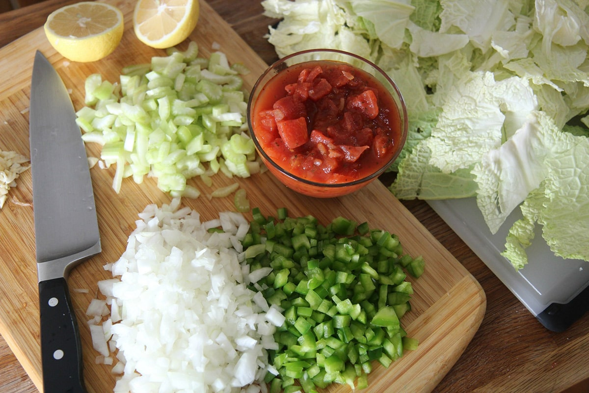 chopped cabbage, onions, tomatoes, lemons, and peppers on a wooden board.