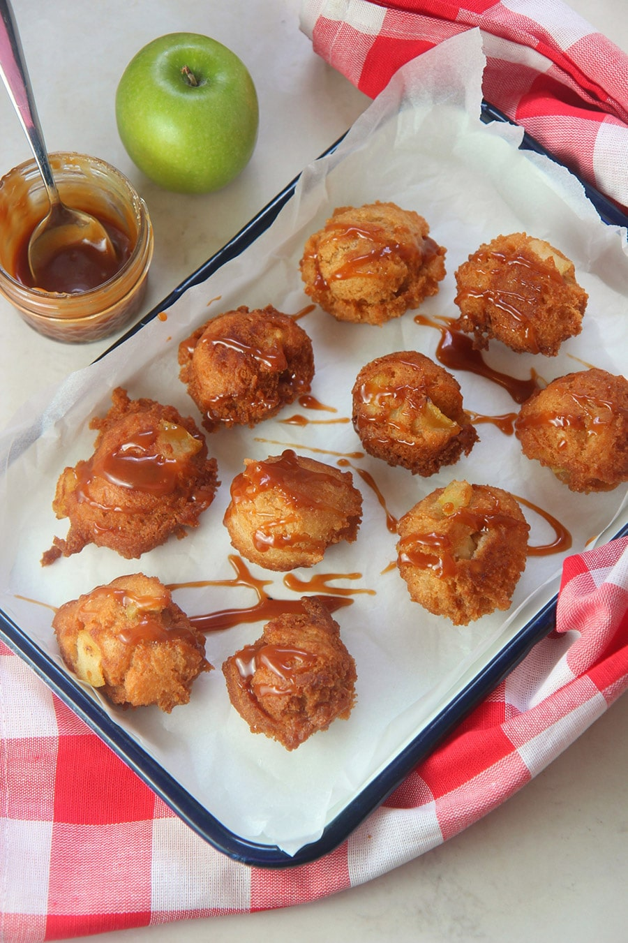 ten fried apple fritters with caramel sauce on top. A small jar of caramel on the side, a green apple, and a red and white towel..