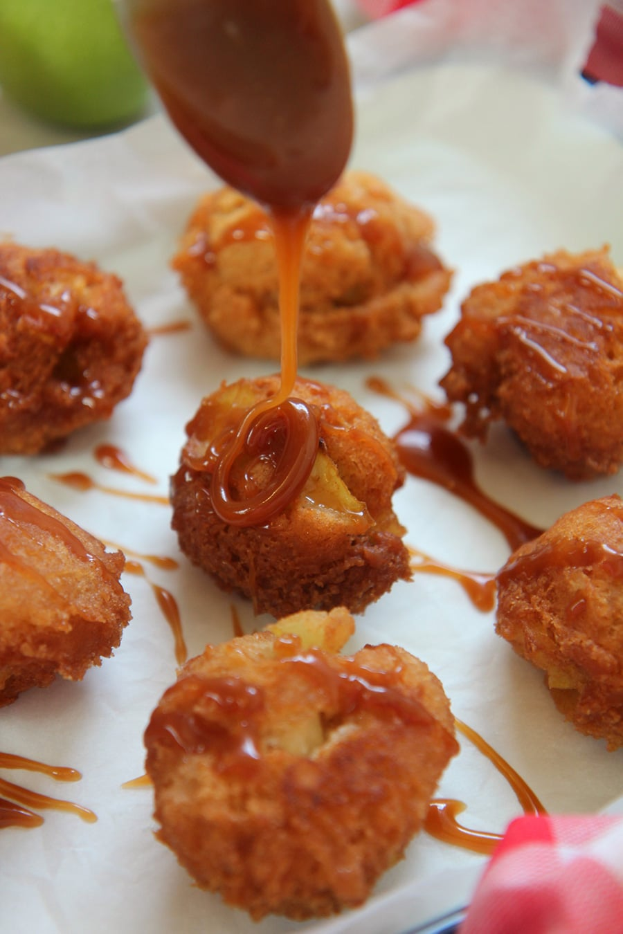 fritters on a white surface with a spoon drizzling caramel sauce on top of one fritter.