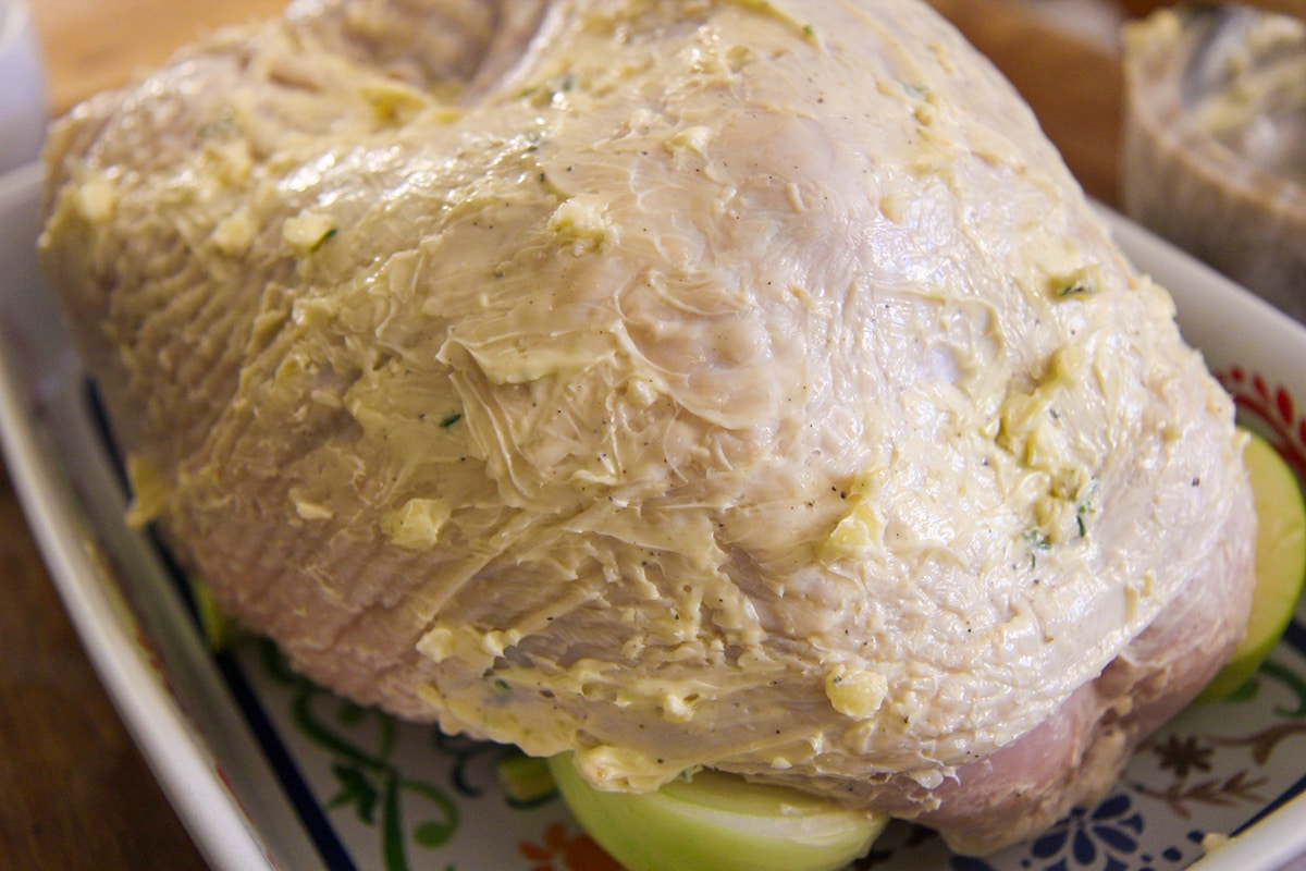 raw turkey breast with butter and garlic all over it.