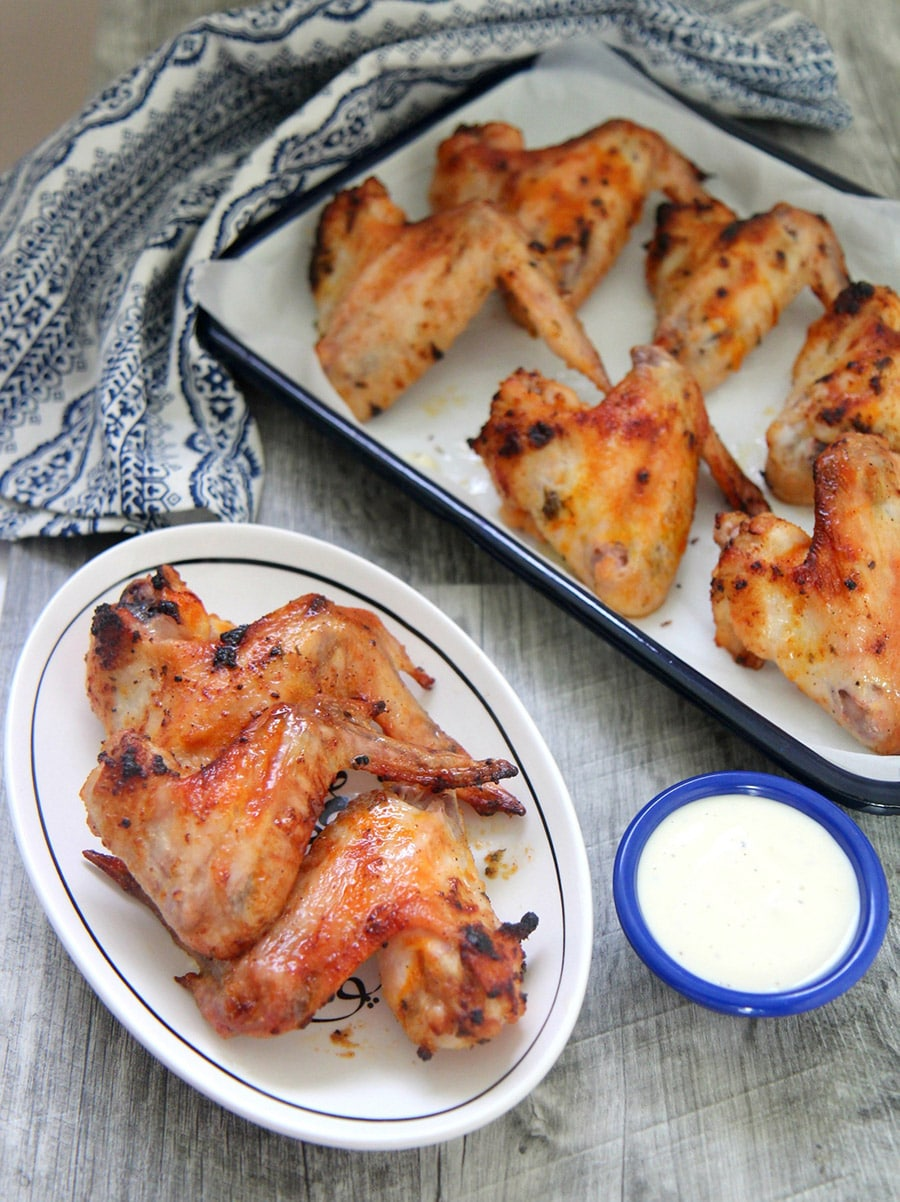 oven roasted chicken wings on a small white plate with a side of blue cheese dip and more chicken wings in the background.
