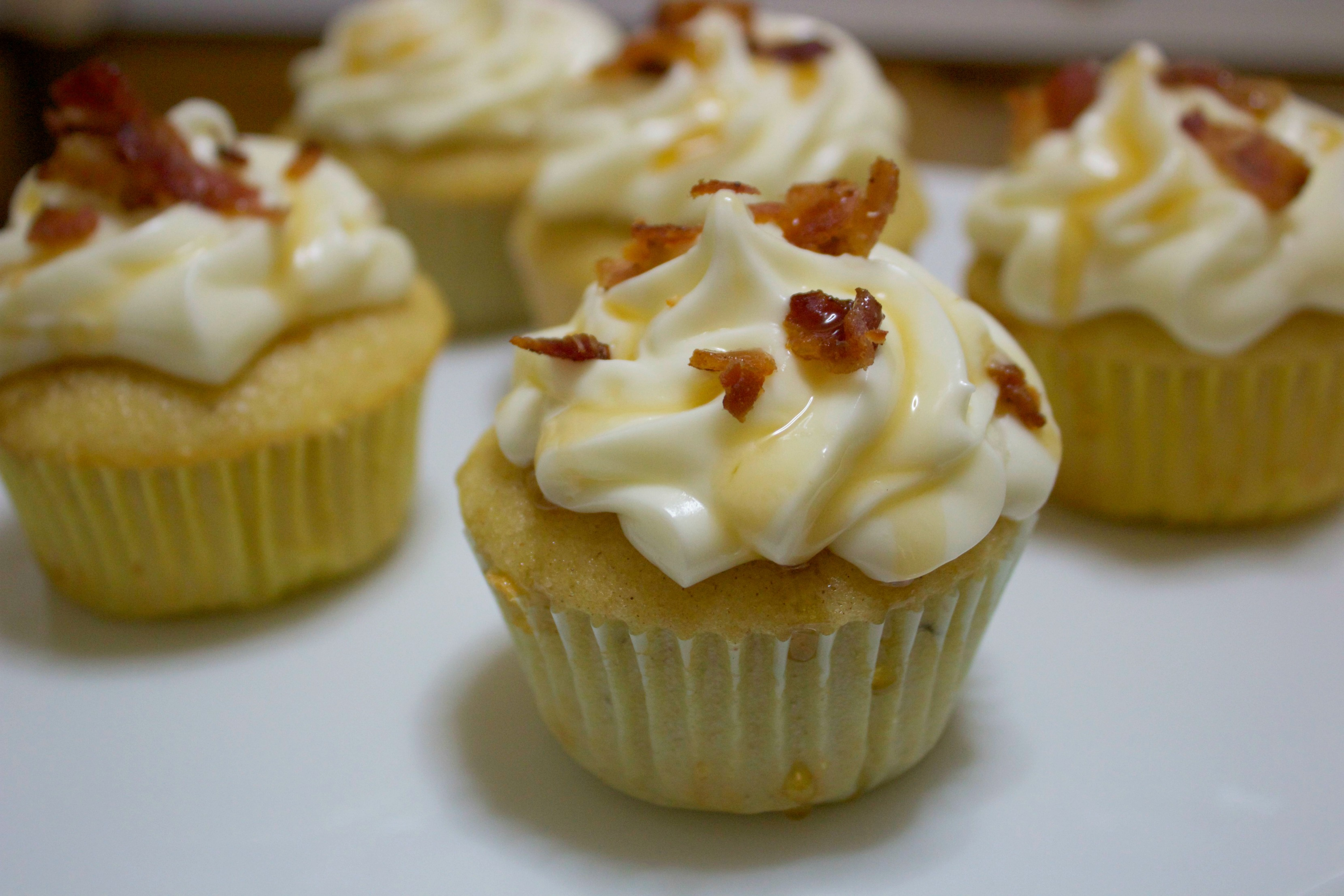 Sweet and savory yellow cupcakes with a cream cheese frosting, syrup drizzle, and bacon bits