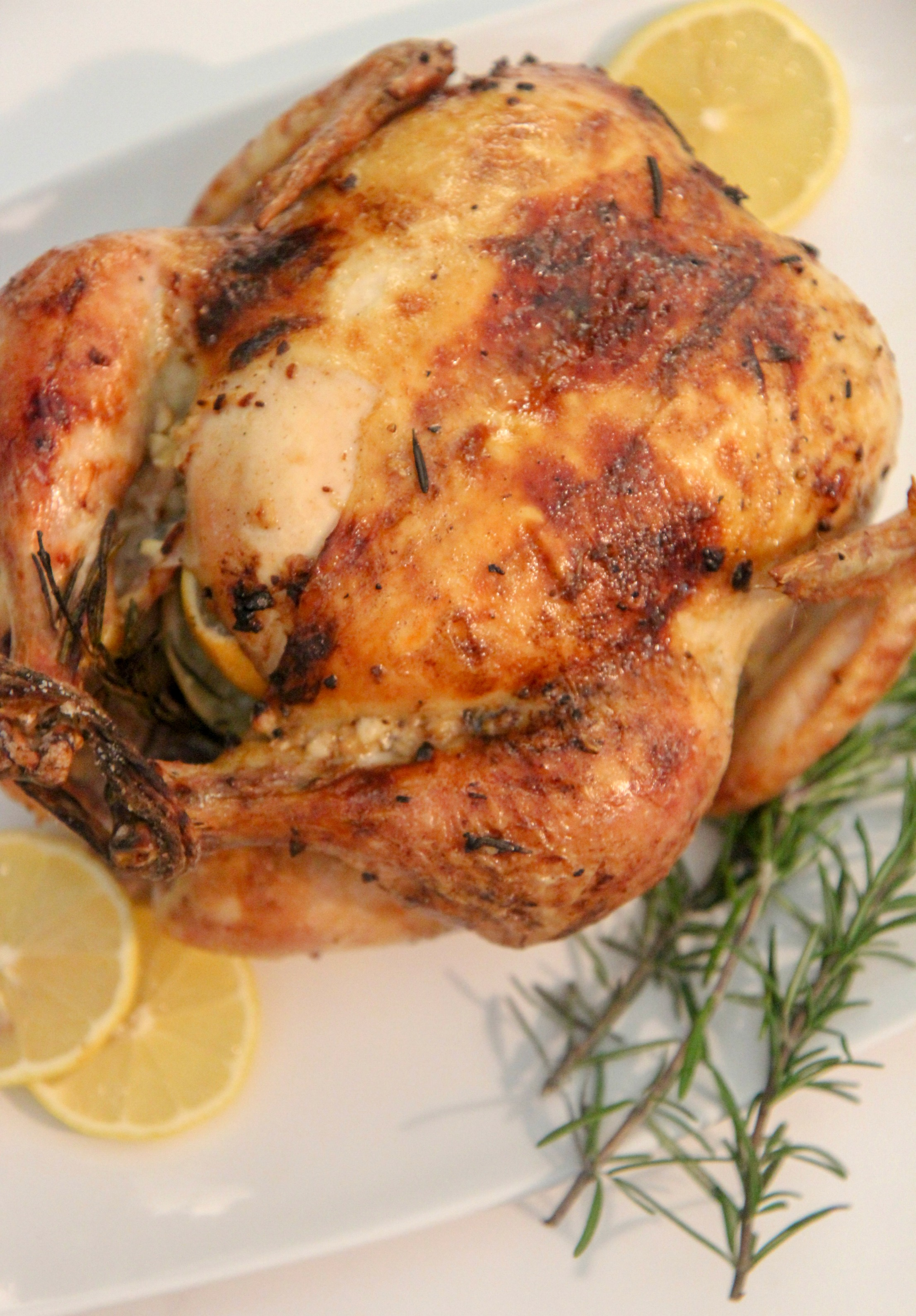 lemon garlic roast chicken on a white platter with rosemary sprigs and lemon slices.