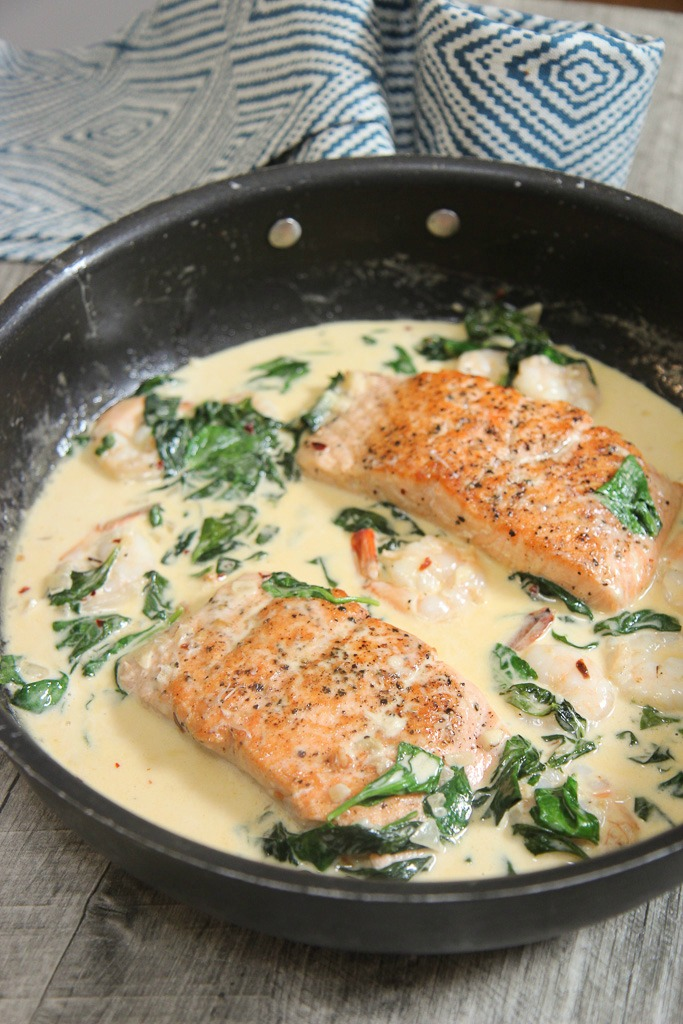 salmon, shrimp, and spinach with a cream sauce in a black skillet.