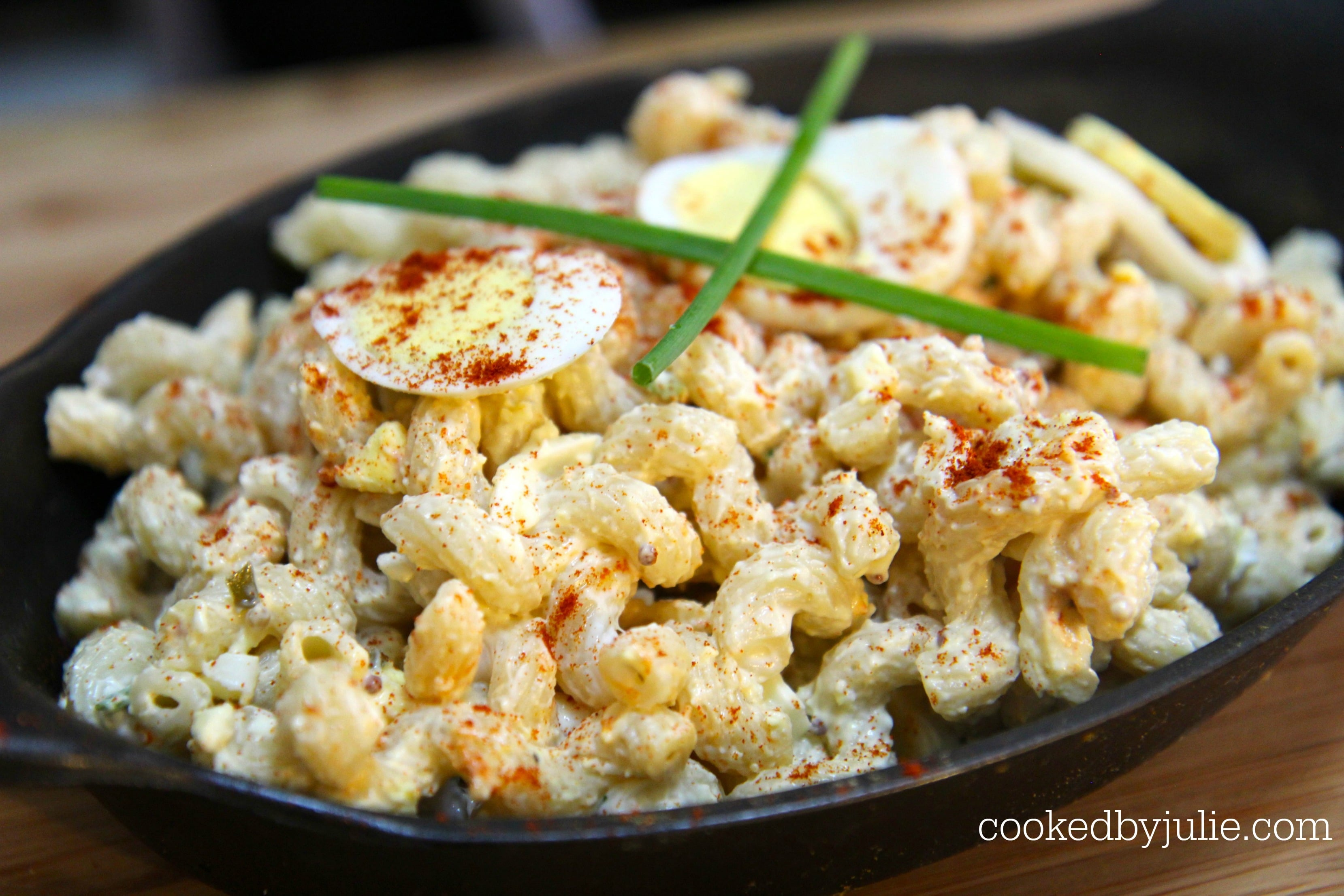 deviled egg pasta salad with hardboiled eggs, paprika, and chives on top.