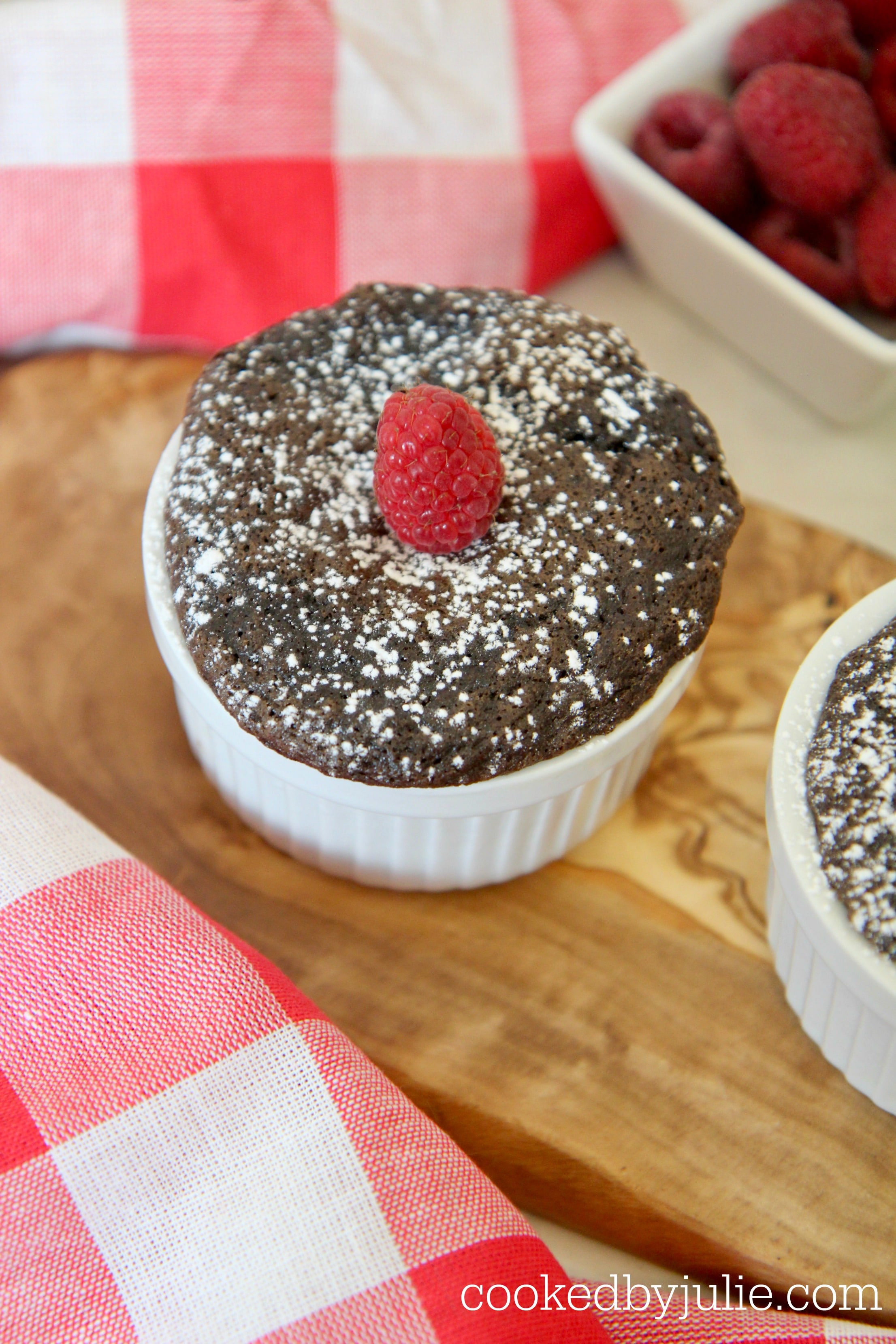 Mini Nutella cakes sprinkled with powdered sugar and topped with raspberries.