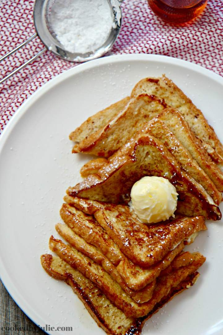 Easy French Toast served with softened butter, powdered sugar, and warm maple syrup.