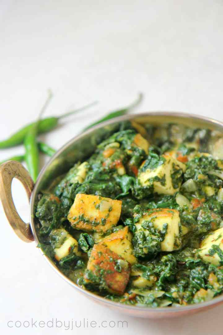 Saag paneer in a gold small dish with green chilies on the side