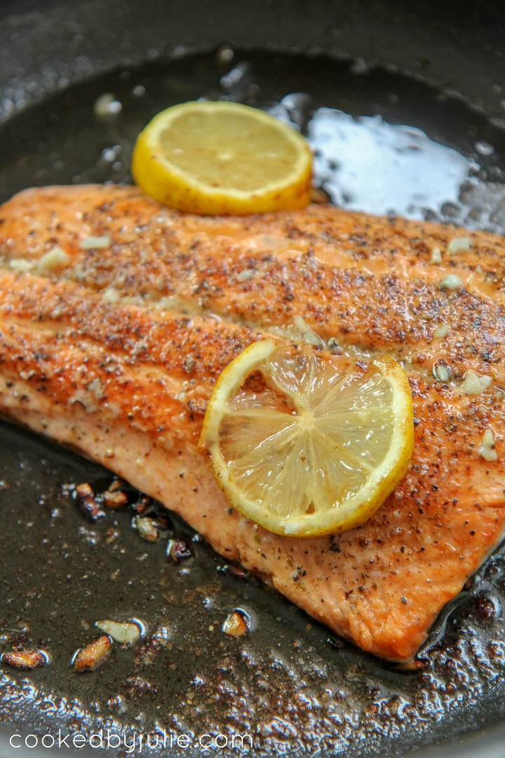 seared salmon with lemon in a black skillet