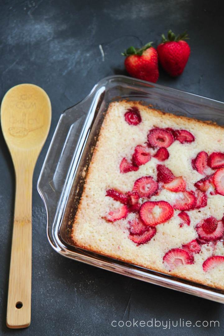 Fresh Strawberry Cobbler in a baking dish with a wooden spoon and two strawberries on the side.