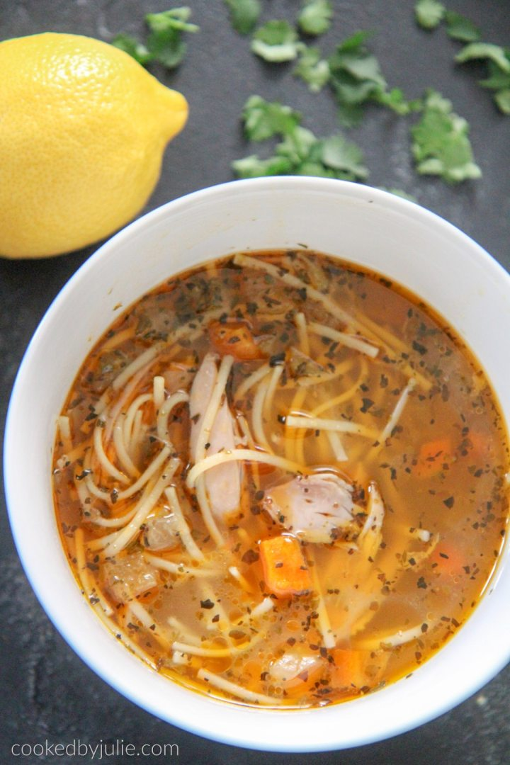 chicken noodle soup in a white bowl with a lemon and parsley on the side.