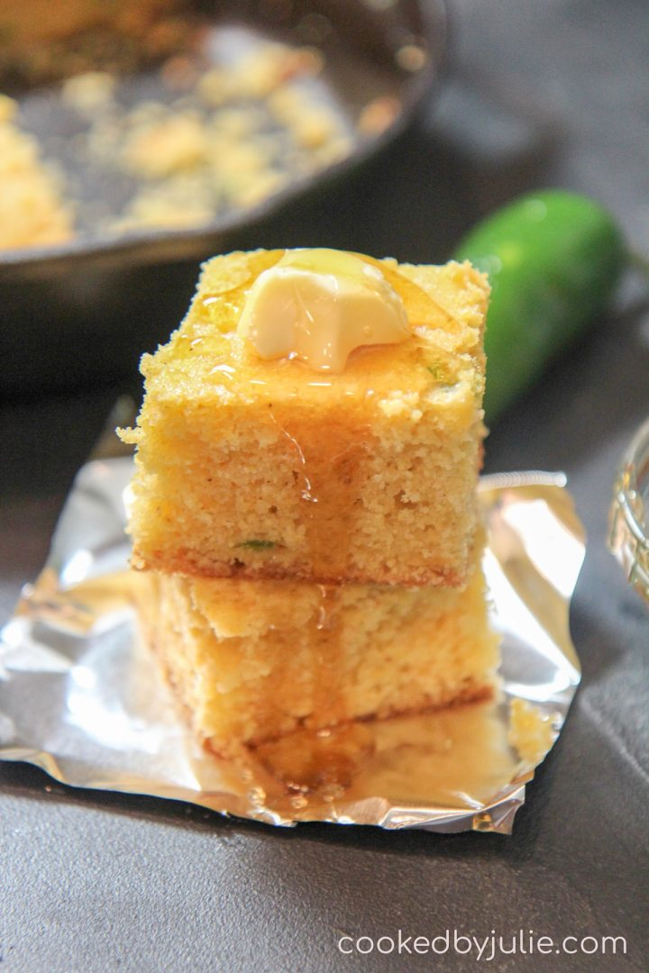 two squared honey cheddar jalapeno cornbread slices on top of aluminum foil with a jalapeno pepper in the back ground and an iron skillet.