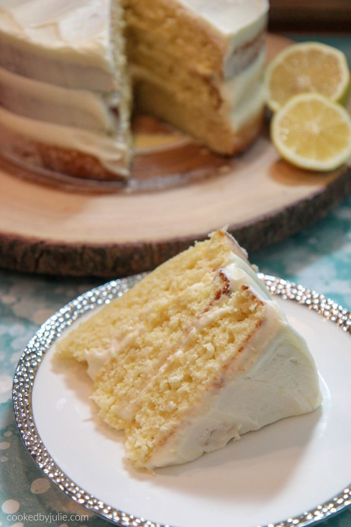 a lemon cake slice on a white and silver plate and a lemon cake in the background on a wooden cake stand with 2 lemon slices.
