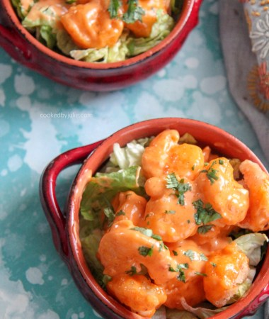 fried shrimp coated in mayo based dressing with fresh parsley on top