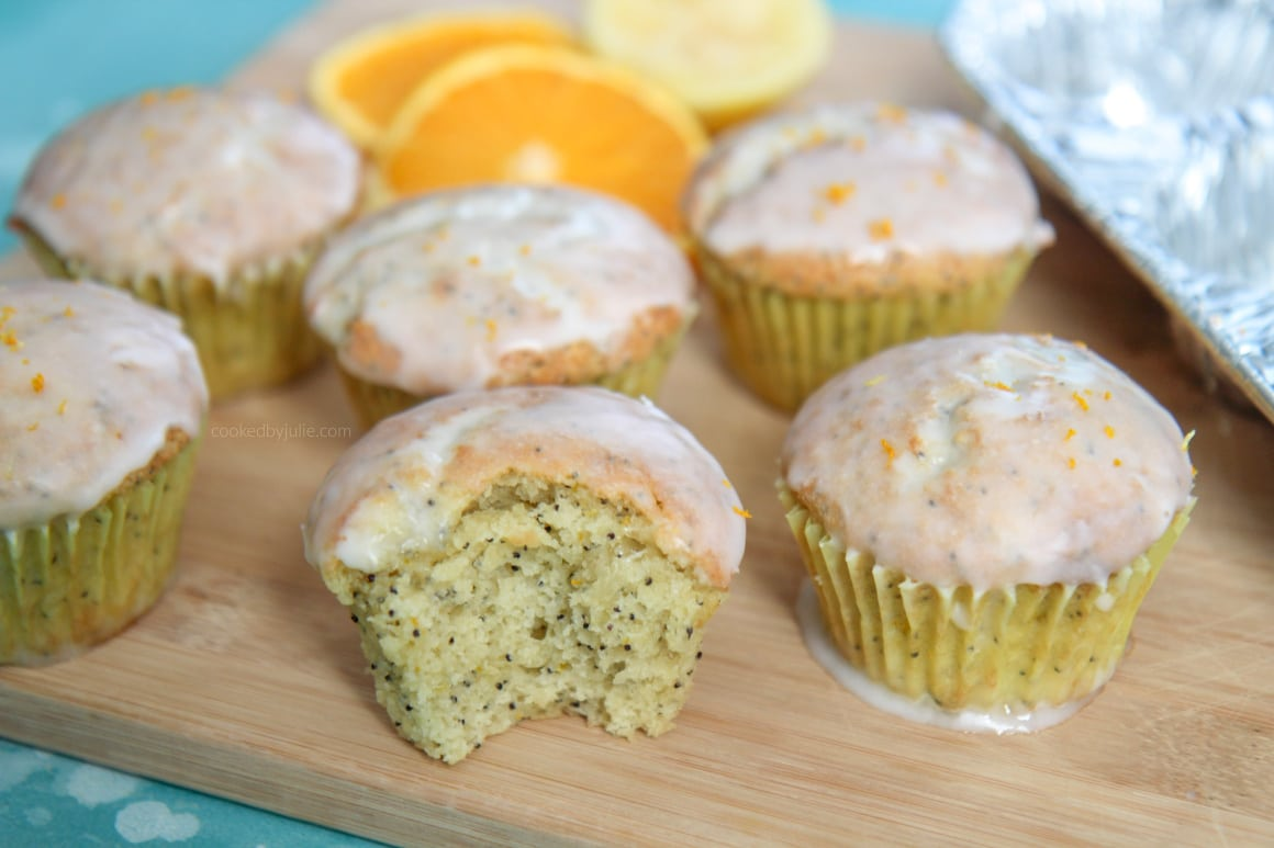 half of a orange lemon poppy seed muffin on top of a wooden board.