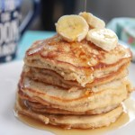six banana pancakes on a white plate with banana slices on top, a drizzle of maple syrup, and a blue mug in the background.
