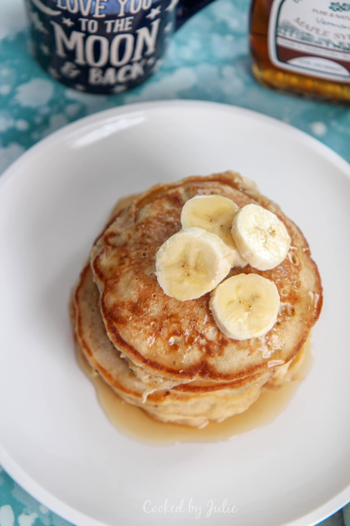 a stack of banana pancakes on a white plate with banana slices and maple syrup