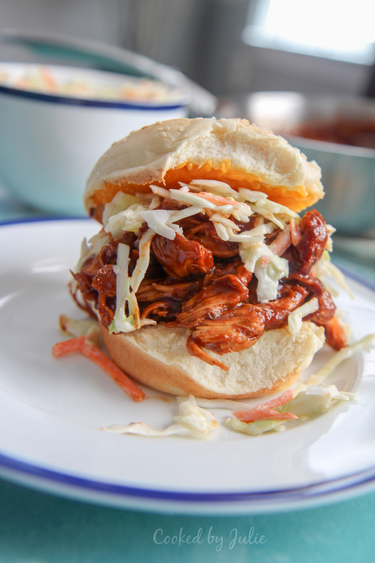 bbq pulled chicken sandwich on top of a white plate with pieces of coleslaw on the plate