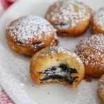 deep fried Oreos with powdered sugar on a white plate with one half eaten cookie and a red and white towel on the side.