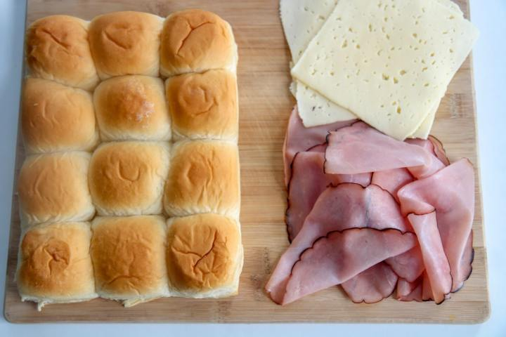 Hawaiian soft rolls with ham and cheese on a wooden board
