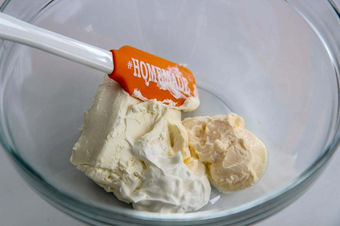 mayo, sour cream, and softened cream cheese in a glass bowl with an orange spatula